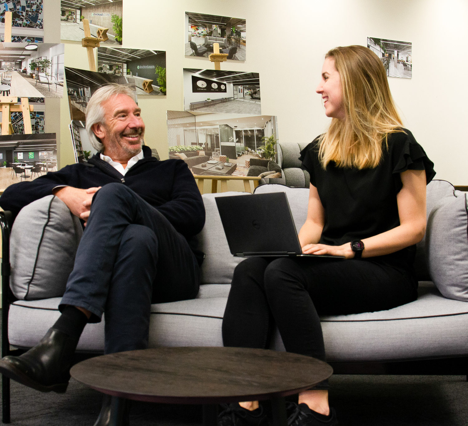Toby and Kate sat on a sofa working collaboratively in the design area smiling